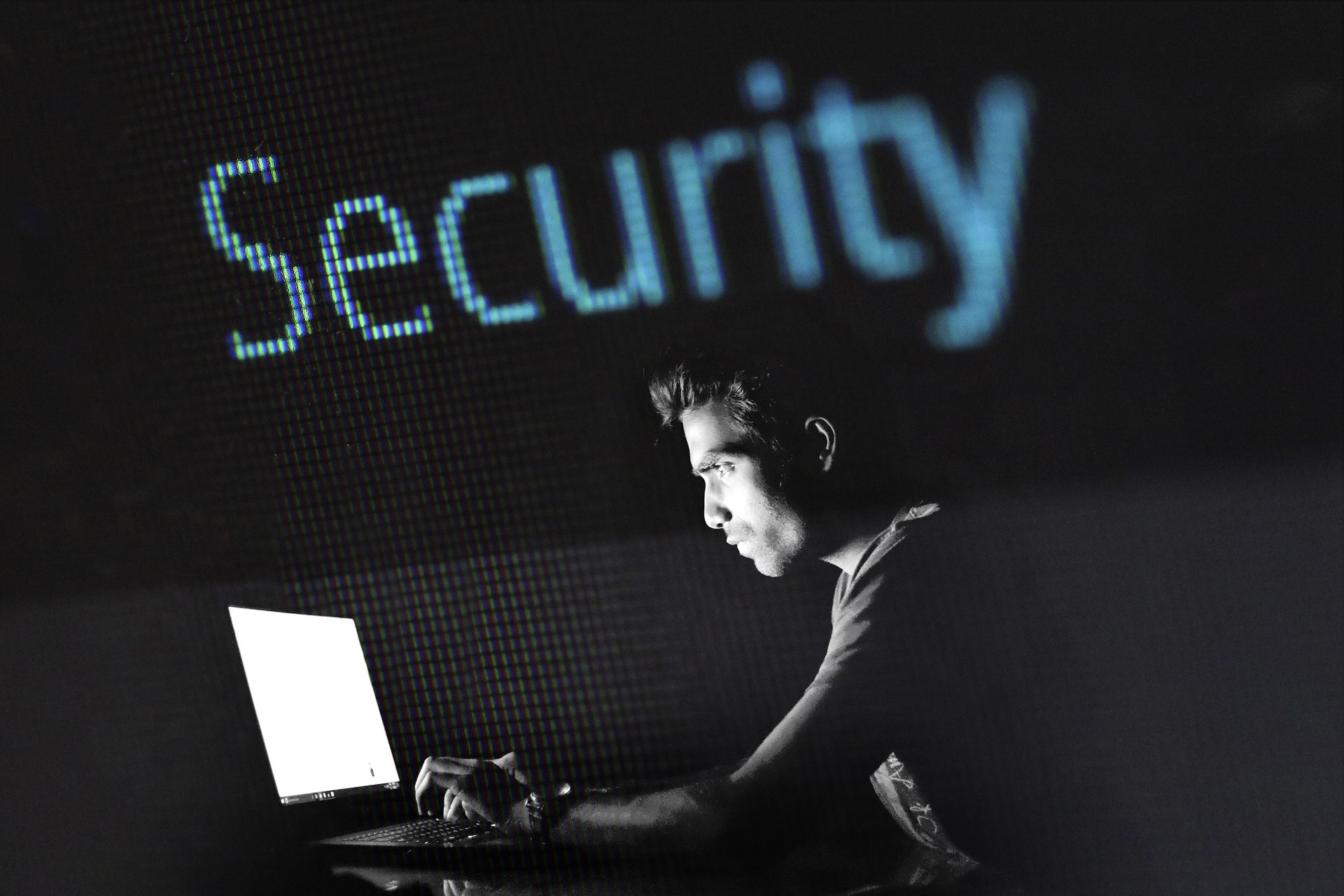 black and white image of a man looking at a bright computer screen with blue text that says security at the top