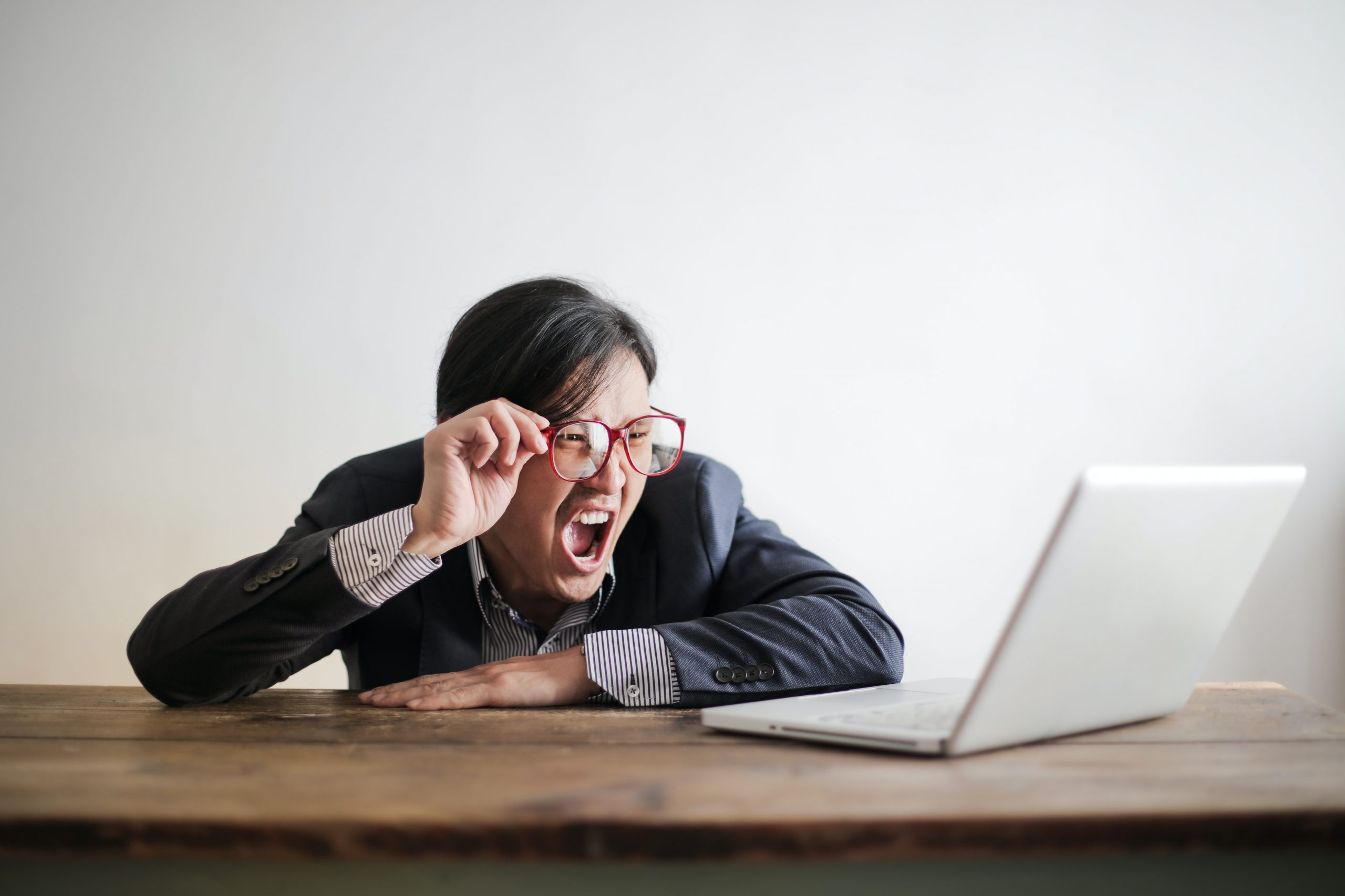 angry business man screaming at laptop